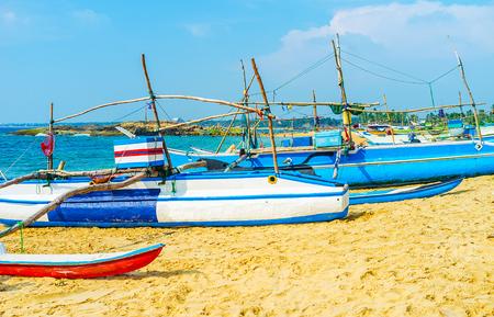 The Dodanduwa harbor is the nice place to discover traditional oruwa boats, standing on the sandy shore, Hikkaduwa, Sri Lanka.