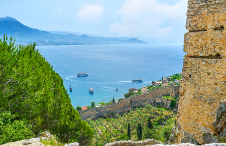The seascape of Alanya with the medieval stone fortress wall, stretching along the Castle hill, Turkey.