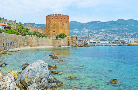 The view on the lower part of Alanya fortress with the stone wall along the beach and arsenal Red Tower next to the port, Turkey.