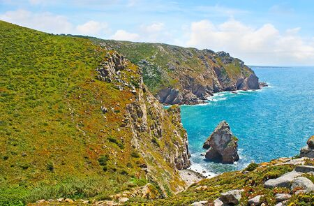 The picturesque coast of Cape Roca with rocky cliffs, covered with hottentot-figs and huge boulders at the shore, Sintra, Portugal.