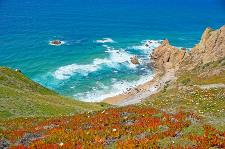 The picturesque Aroeira beach at the foot of the cliff of Cabo da Roca (Cape Roca), the westernmost point of Europe, Sintra, Portugal.