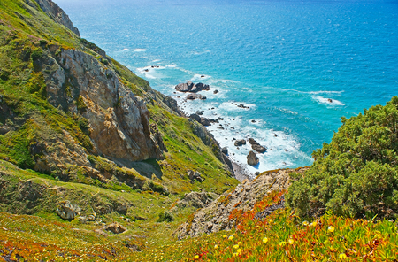 The view from the steep slope of the cliff on the secret beach, hidden among the rocks of Cape Roca, Sintra, Portugal.