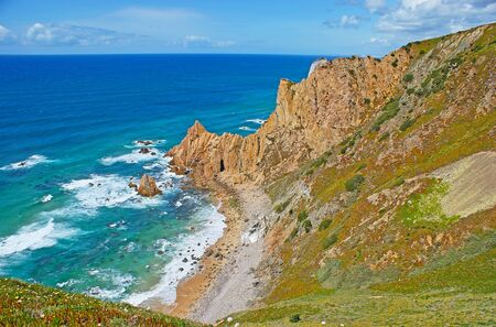 The scenic Aroeira beach located in small natural harbor among the cliffs of Cape Roca, Sintra, Portugal.