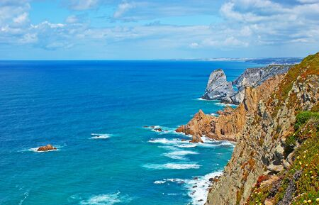 The rocky edge of the Cabo da Roca with huge boulders in Atlantic Ocean, Sintra, Portugal.