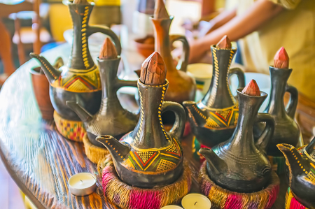 Traditional Ethiopian pottery jebena boiling pots for the ethnic coffee ceremony are decorated with colored patterns, has handmade wooden lids and the stands under the hot, made of grass rope.