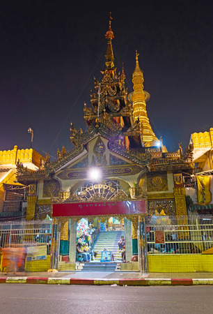 YANGON, MYANMAR - FEBRUARY 14, 2018: The brichly decorated gate of Sule Pagoda with carved roof in evening lights, on February 14 in Yangon.