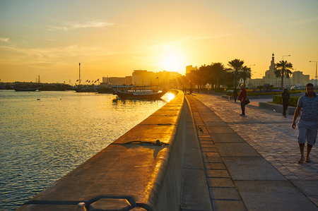 DOHA, QATAR - FEBRUARY 13, 2018: The sunrise over the Corniche promenade with a view on traditional dhow boats in harbor and row of palms along the way, on February 13 in Doha.