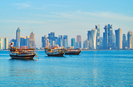 The tourist harbor opens the view on modern Doha - skyscrapers of coastal Al Dafna district are seen behind the boats, Qatar.