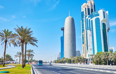 DOHA, QATAR - FEBRUARY 13, 2018: The palms of Sheraton park stretch along the automobile road in Corniche street, separating coastal promenade and skyscrapers of West Bay neighborhood, on February 13 in Doha.
