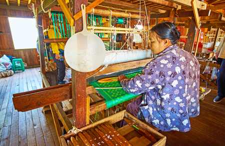 INPAWKHON, MYANMAR - FEBRUARY 18, 2018: Textile workshops on Inle lake are famous for the high quality handmade fabrics of cotton, silk and lotus, produced by locals, on February 18 in Inpawkhon.