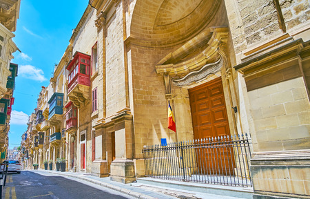 Ensemble of medieval St Ursula street includes the Baroque Church of St Roque and traditional edifices with bright Maltese balconies, Valletta, Malta.