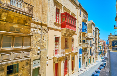 The view from the upper terrace on the gentle descent in St Ursula street with line of old edifices, with colored Maltese balconies, Valletta, Malta.