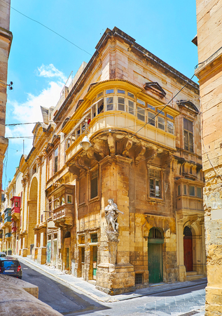 The niche statue of St Roque in corner of the historical edifice in St Christopher and St Ursula streets intersection, Valletta, Malta.