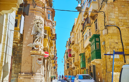 The niche or corner statues are very popular architectural detail in Valletta, such as statue of St Michael the Archangel, fighting the Satan, on corner of Archbishop and St Ursula streets, Valletta, Malta.