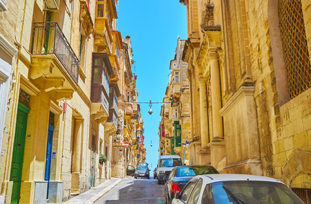 Walk along the ascent in St Ursula street with a view on historical housing and colored Maltese balconies, Valletta, Malta.
