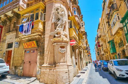 VALLETTA, MALTA - JUNE 17, 2018: Panorama of St Ursula street with the corner stucco statue of St Michael, fighting the devil, on June 17 in Valletta.