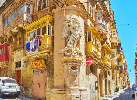 VALLETTA, MALTA - JUNE 17, 2018: The corner statue, also named the niche of St Michael, fighting the Satan, decorates the old edifice in of Archbishop's and St Ursula's streets intersection, on June 17 in Valletta.