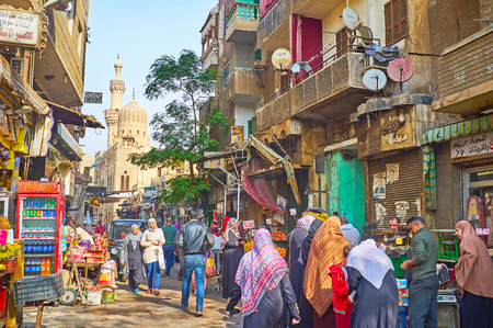 CAIRO, EGYPT - DECEMBER 21, 2017: The crowded Al Khayama street with many food stalls and medieval Prince Gani Bek mosque on the background, on December 21 in Cairo.