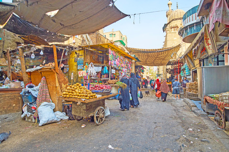 CAIRO, EGYPT - DECEMBER 21, 2017: The shabby food stalls and old wooden carts with fresh vegetables in farmers market of Al Khayama street, on December 21 in Cairo.