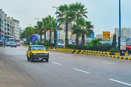 ALEXANDRIA, EGYPT - DECEMBER 19, 2017: The vintage taxi drives along the Corniche Avenue with a line of green palms on the background, on December 19 in Alexandria.
