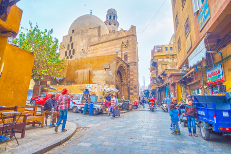 CAIRO, EGYPT - DECEMBER 20, 2017: The famous grocery market in EL Gamaleya street around huge Al Zaher mosqu and bored merchants smoke  egyptian hookahs, on December 20 in Cairo.