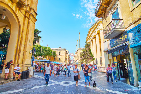 Photo for VALLETTA, MALTA - JUNE 18, 2018: Republic street is central pdestrian area of the city with large amount of fshion stores, souvenir stalls, tourist cafes and historical landmarks, on June 18 in Valletta. - Royalty Free Image