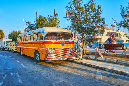 Photo for SLIEMA, MALTA - JUNE 19, 2018: The vintage AEC-Reliance bus, parked at the seaside promenade, serves as the souvenir store and attracts the tourists, walking around the harbor, on June 19 in Sliema - Royalty Free Image