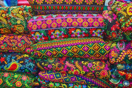 Photo for The heap of embroidered textiles, tapestries and bedcovers with colorful floral and authentic patterns in shop of Vakil Bazaar, Shiraz, Iran - Royalty Free Image
