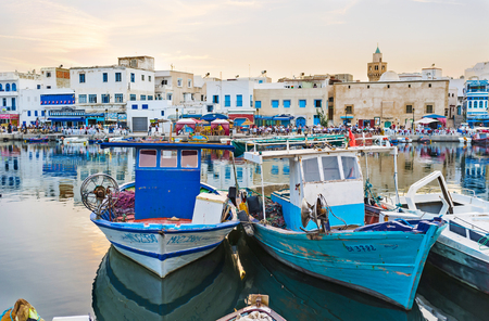 Photo pour BIZERTE, TUNISIA - SEPTEMBER 4, 2015: The moored boats in old port with busy old town quarter on the background, on September 4 in Bizerte - image libre de droit