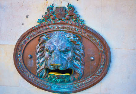 CADIZ, SPAIN - SEPTEMBER 24, 2019: The scenic bronze lion-head post box with open mouth for corrspondence, located on the wall of post office, on September 24 in Cadiz
