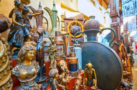 Photo pour The vintage items (figurines, dallah coffee pots, lamps) on the counter of the vintage shop, Souk Madinat Jumeirah market, Dubai, UAE - image libre de droit