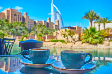 Photo pour Enjoy hot black coffee in outdoor cafe of Souk Madinat Jumeirah market, sitting at the canal with a view on Burj al Arab in the background, Dubai, UAE - image libre de droit