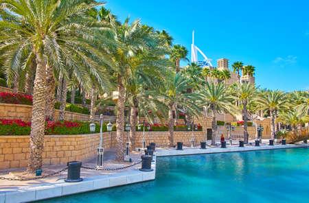 Photo pour Enjoy the scenic terrace park with shady palms and colorful flower beds, located along the canal of Souk Madinat Jumeirah market, Dubai, UAE - image libre de droit