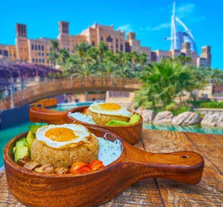 Photo pour The tasty lunch on the outdoor terrace of the restaurant in Souk Madinat Jumeirah, enjoy amaranth porridge, fried eggs, grilled veggies and a view on Burj al Arab, Dubai, UAE - image libre de droit