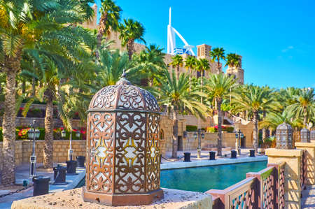 Photo pour The line of beautiful Arabian lamps along the bank of the canal with shady green park in the background, Souk Madinat Jumeirah market, Dubai, UAE - image libre de droit