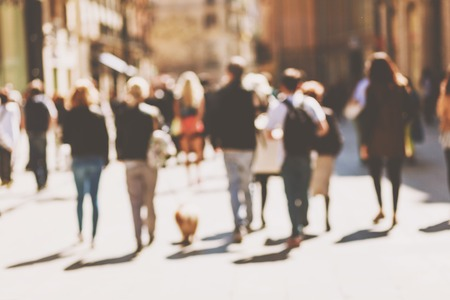 Photo pour Blurred crowd of walking people in the city with buildings in the background - image libre de droit