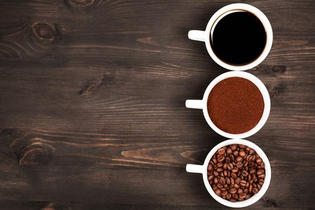 Foto de Three cups with different states or stages, or conditions, or black coffee. Dark wooden background. - Imagen libre de derechos