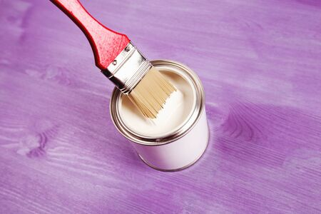 Dip brush into the paint. Paint is dripping from brush to a jar.