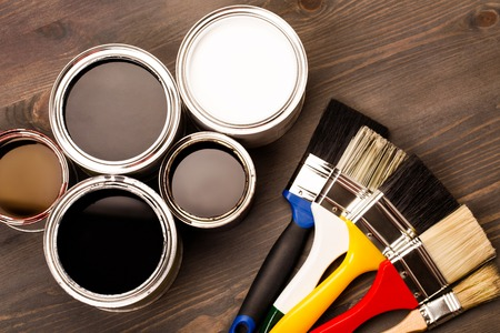 Photo pour House renovation, paint cans and colored brushes on the wooden grey background - image libre de droit