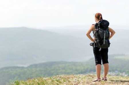 Foto de Woman with backpack on green hill. - Imagen libre de derechos