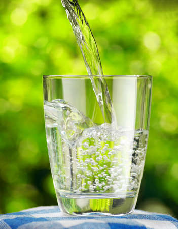 Glass of water on nature background.の写真素材