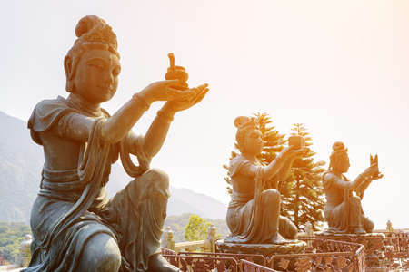 Buddhist statues praising and making offerings to the Tian Tan Buddha (the Big Buddha) in sunlight at Lantau Island, in Hong Kong. Hong Kong is popular tourist destination of Asia.