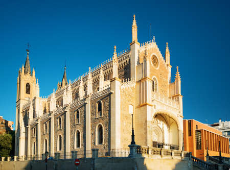View of the San Jeronimo el Real (St. Jerome Royal Church) in evening sun. Roman Catholic church located in central Madrid, Spain. Blue sky in background.