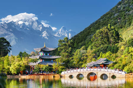 Amazing view of the Jade Dragon Snow Mountain and the Suocui Bridge over the Black Dragon Pool in the Jade Spring Park, Lijiang, Yunnan province, China.