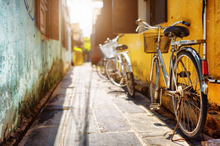 Photo pour Bicycles parked near yellow wall of old house on sunny street in summer. Hoi An Ancient Town (Hoian), Vietnam. Hoi An Ancient Town is a popular tourist destination of Asia. - image libre de droit