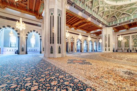 Foto de Muscat, Oman - 17 October, 2018: Beautiful carpet in the main prayer hall of the Sultan Qaboos Grand Mosque. Wonderful interior of the Muslim place. Amazing Islamic architecture and decoration. - Imagen libre de derechos