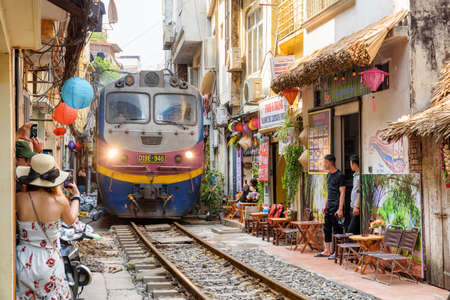 Photo pour Hanoi, Vietnam - April 18, 2019: Incredible view of train passing through a narrow street, the Hanoi Old Quarter. Tourists taking pictures of the train. The Hanoi Train Street is a popular attraction. - image libre de droit