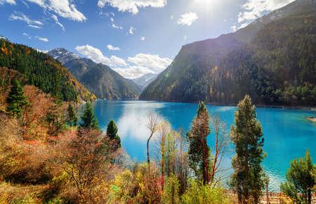 Foto de Fantastic view of the Long Lake with azure water among colorful fall woods and mountains in Jiuzhaigou nature reserve (Jiuzhai Valley National Park), China. Amazing sunny autumn landscape. - Imagen libre de derechos
