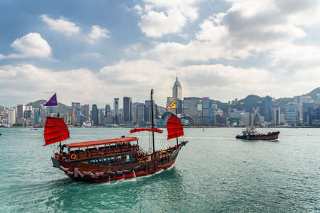 Photo pour Hong Kong - October 20, 2017: Awesome view of traditional Chinese wooden sailing ship with red sails in Victoria harbor. Hong Kong Island skyline on sunny day. Amazing cityscape. - image libre de droit