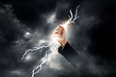 business woman hand clenching lightning flash